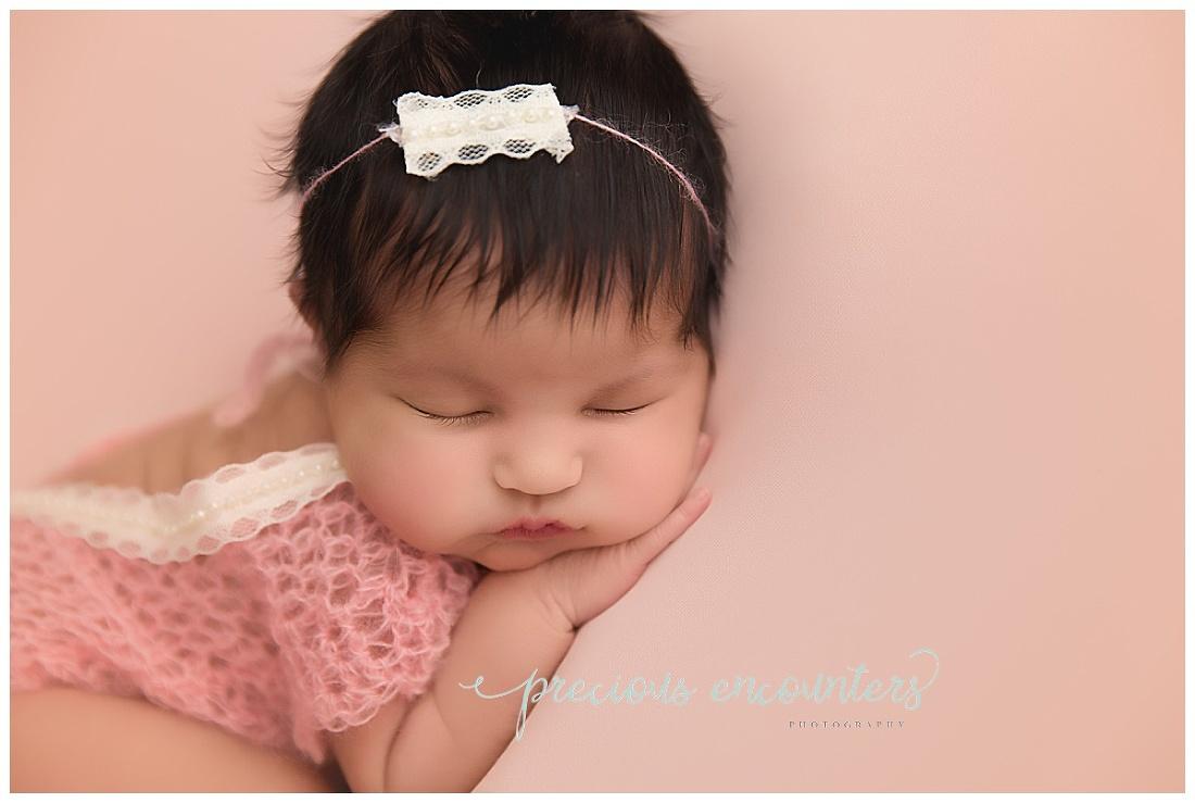 newborn, girl, pink, romper, posed, closeup